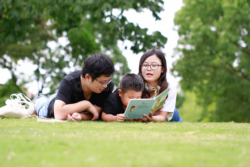 Glückliches Latinofamilien-Lesebuch stockbilder