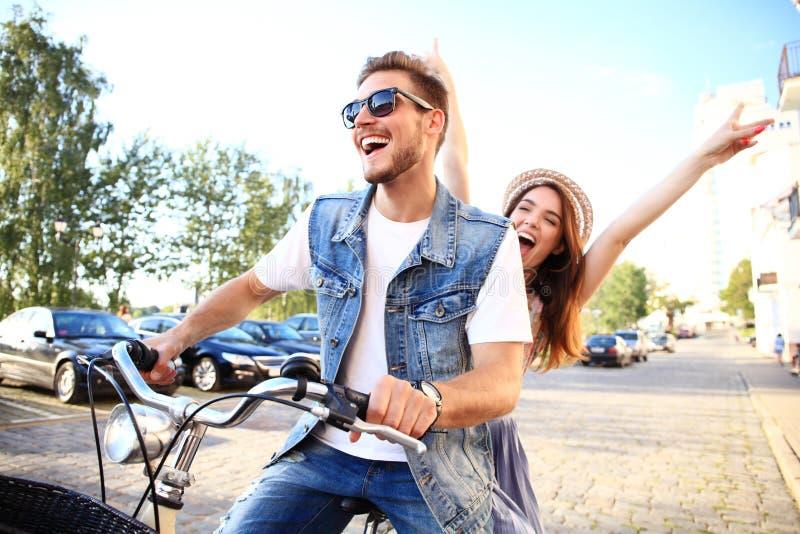 Glückliches lustiges junges Paarreiten auf Fahrrad stockbilder