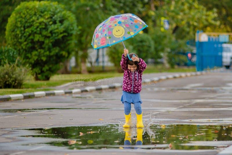 Glückliches lustiges Kind mit springenden Pfützen des mehrfarbigen Regenschirmes in den Gummistiefeln und im Lachen lizenzfreies stockbild