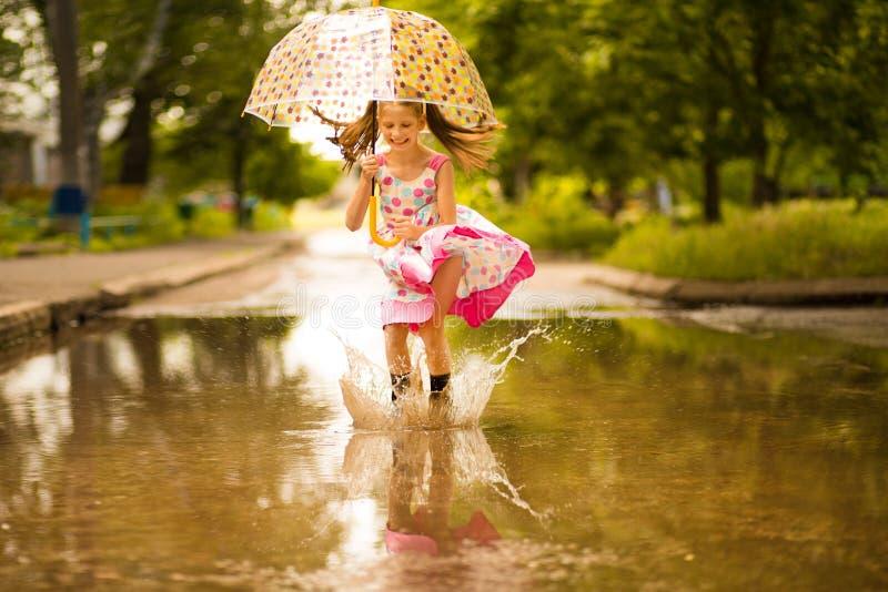 Glückliches lustiges Kindermädchen mit dem Regenschirm, der auf Pfützen in den Gummistiefeln und im Kleid und im Lachen springt lizenzfreie stockfotografie