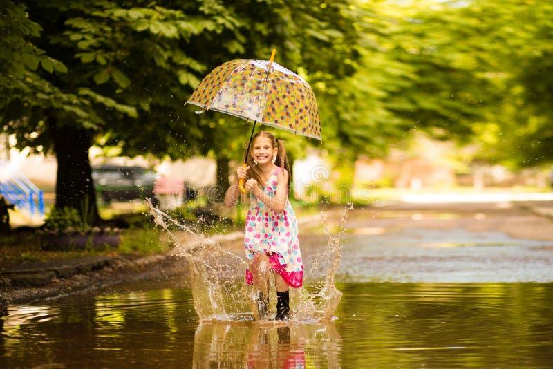 Glückliches lustiges Kindermädchen mit dem Regenschirm, der auf Pfützen in den Gummistiefeln und im Kleid und im Lachen springt stockbild
