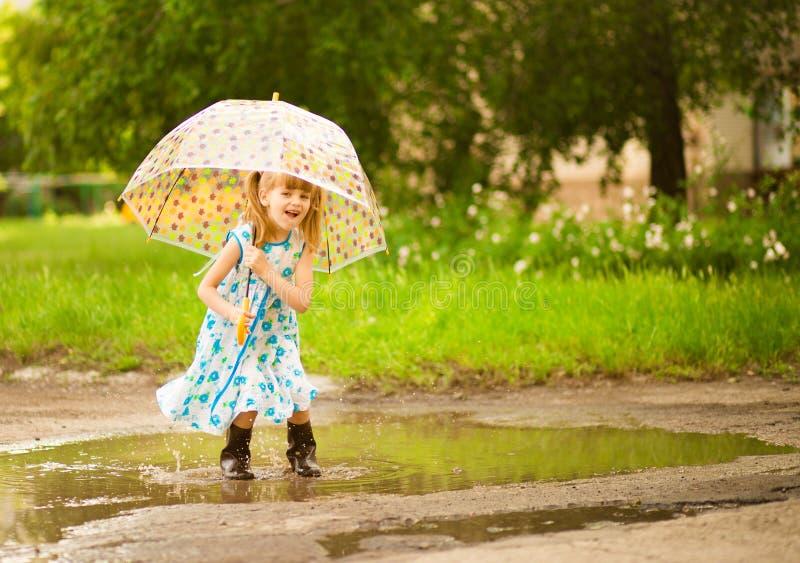 Glückliches lustiges Kindermädchen mit dem Regenschirm, der auf Pfützen in den Gummistiefeln und im Kleid und im Lachen springt stockfotos