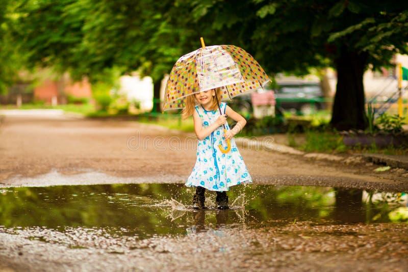 Glückliches lustiges Kindermädchen mit dem Regenschirm, der auf Pfützen in den Gummistiefeln und im Kleid und im Lachen springt lizenzfreie stockfotos