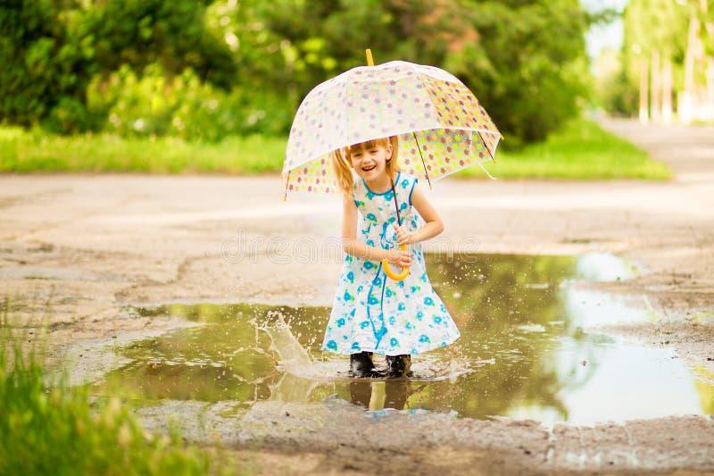 Glückliches lustiges Kindermädchen mit dem Regenschirm, der auf Pfützen in den Gummistiefeln und im Kleid und im Lachen springt stockfoto