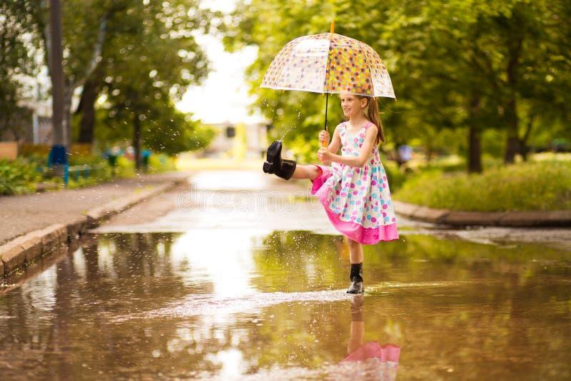 Glückliches lustiges Kindermädchen mit dem Regenschirm, der auf Pfützen in den Gummistiefeln und im Tupfenkleid springt stockfoto