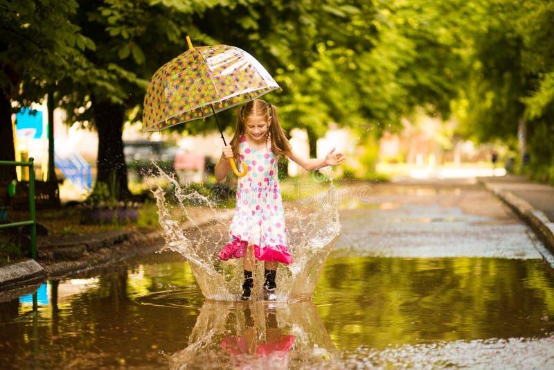 Glückliches lustiges Kindermädchen mit dem Regenschirm, der auf Pfützen in den Gummistiefeln und im Tupfenkleid springt lizenzfreies stockfoto