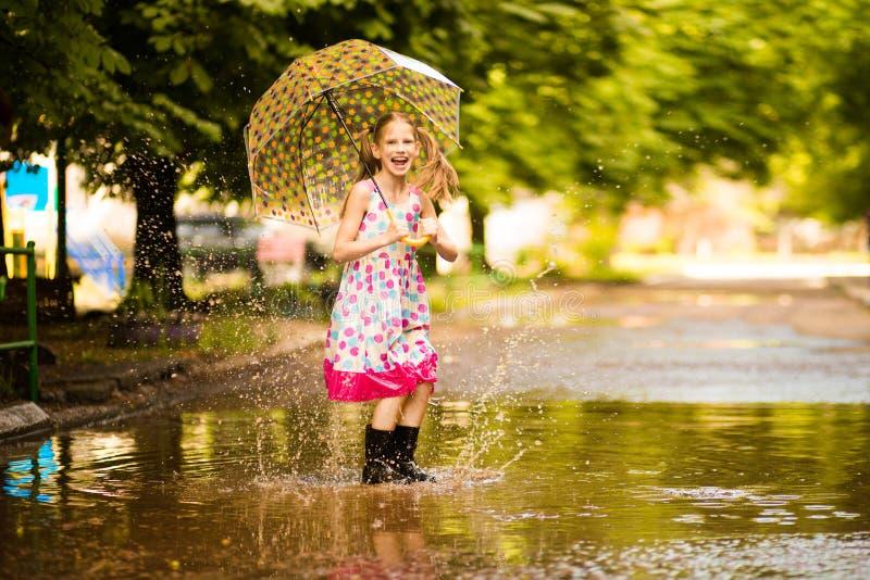 Glückliches lustiges Kindermädchen mit dem Regenschirm, der auf Pfützen in den Gummistiefeln und im Tupfenkleid springt stockfotografie