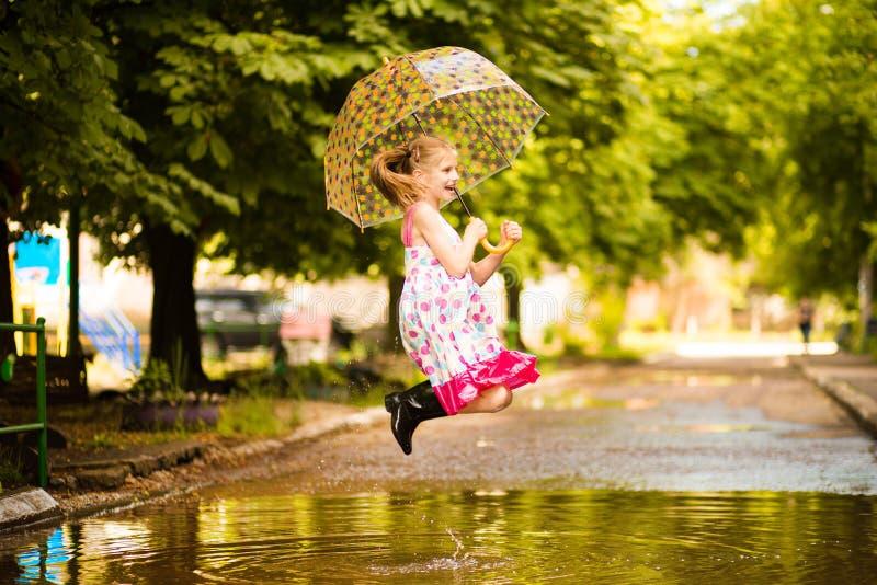 Glückliches lustiges Kindermädchen mit dem Regenschirm, der auf Pfützen in den Gummistiefeln und im Tupfenkleid springt stockfotos