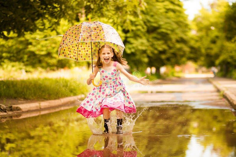 Glückliches lustiges Kindermädchen mit dem Regenschirm, der auf Pfützen in den Gummistiefeln und im Tupfenkleid springt stockbild