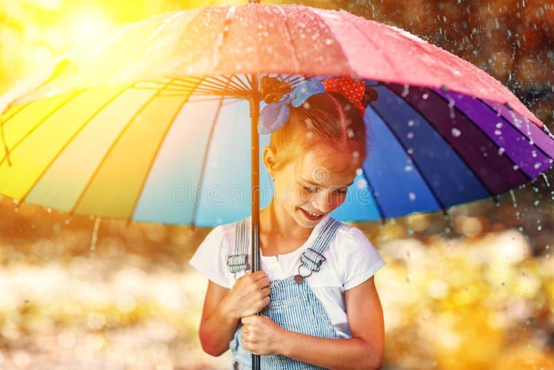 Glückliches lustiges Kindermädchen mit dem Regenschirm, der auf Pfützen im rubb springt lizenzfreies stockbild