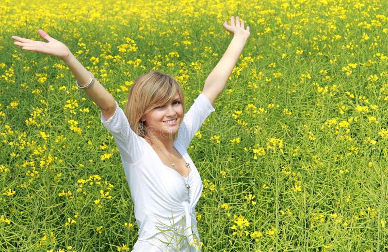 Glückliches Mädchen auf dem Blumengebiet lizenzfreie stockfotos