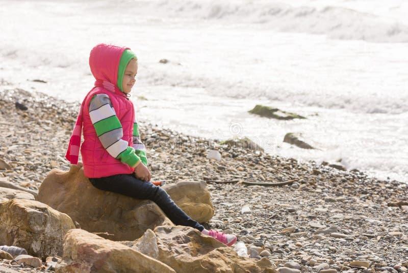 Glückliches Mädchen, das auf einem Felsen auf Seeküste sitzt und den Abstand untersucht lizenzfreie stockbilder