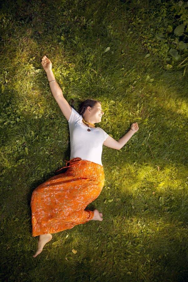 Glückliches Mädchen, das auf grünem Gras sich entspannt stockfotos