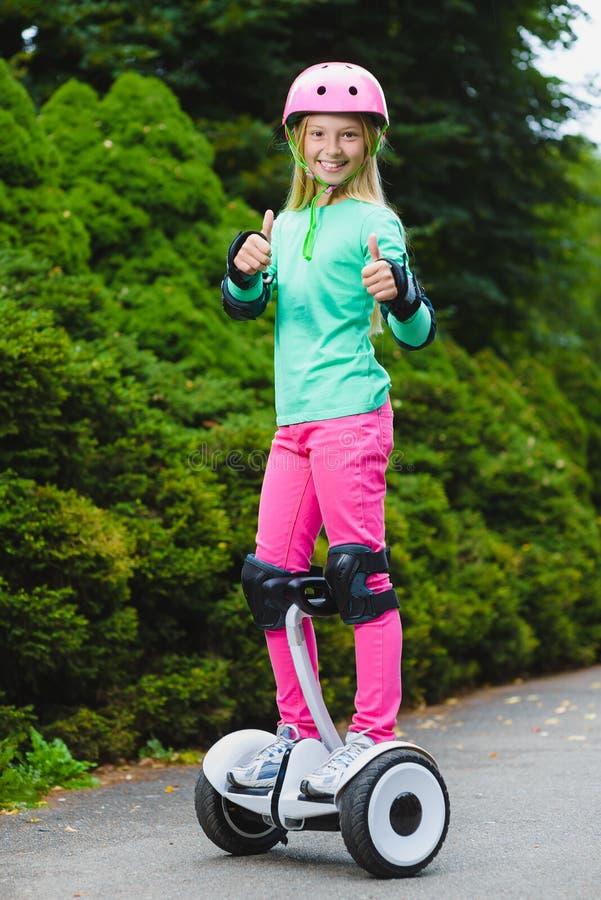 Glückliches Mädchen, das auf hoverboard stehen oder gyroscooter im Freien stockbild