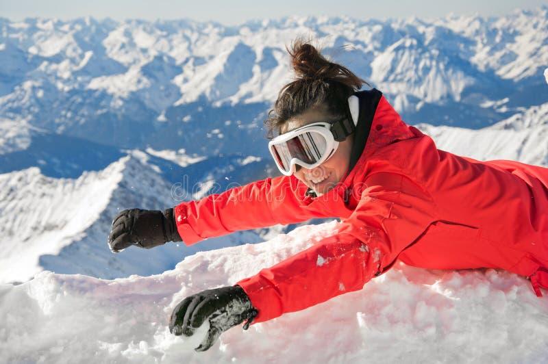 Glückliches Mädchen, das auf Schnee auf einem Berg wellenartig bewegt stockbilder