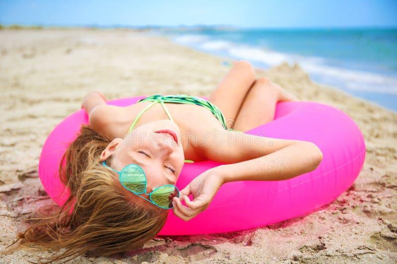 Glückliches Mädchen, das auf Strand ein Sonnenbad nimmt stockfoto