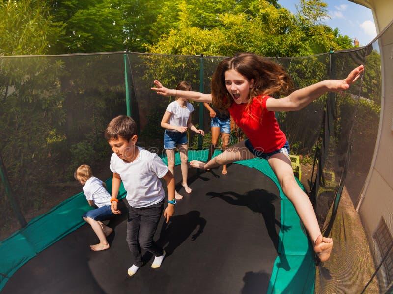 Glückliches Mädchen, das auf Trampoline mit ihren Freunden springt stockbilder