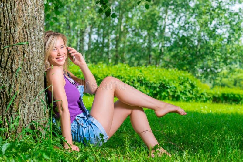 Glückliches Mädchen, das den Spaß spricht am Telefon hat stockfotografie