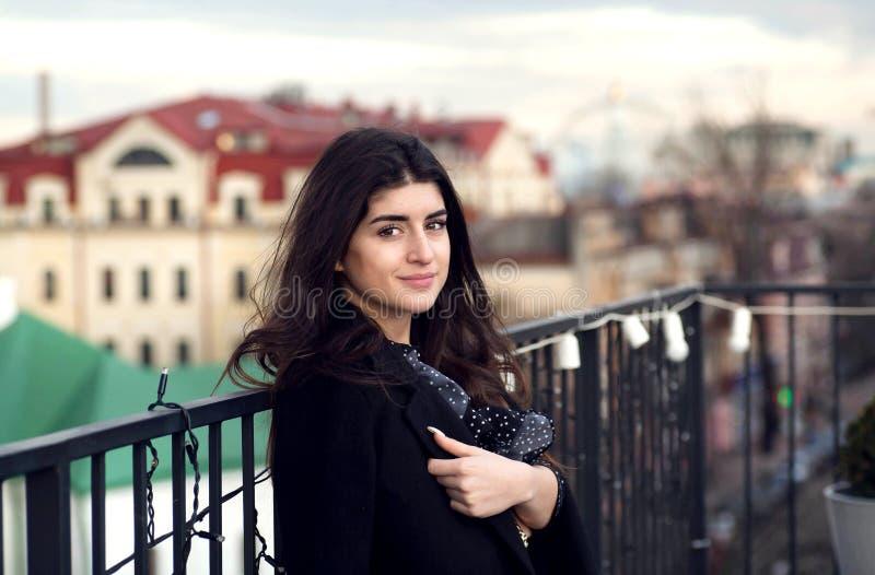 Glückliches Mädchen, das an der Dachspitze über Stadt lächelt und aufwirft Junge brunette Frau, die an alles im Stadtgebiet denkt stockfoto