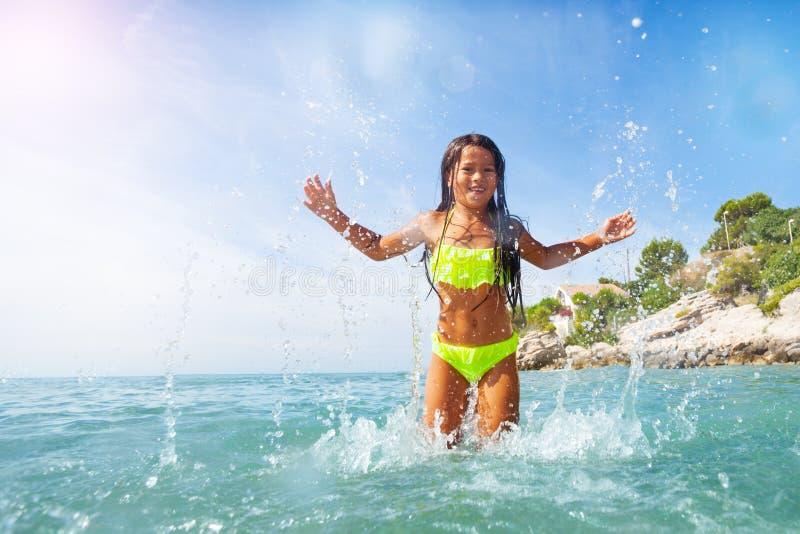 Glückliches Mädchen, das an der Küste spritzt und spielt lizenzfreie stockfotos