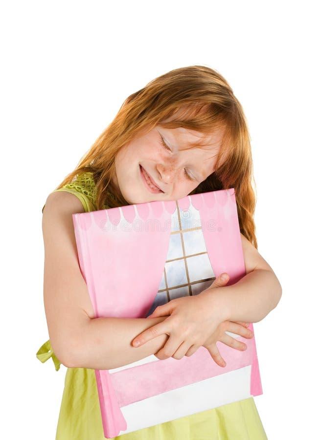 Glückliches Mädchen, das ein Buch anhält stockfotos
