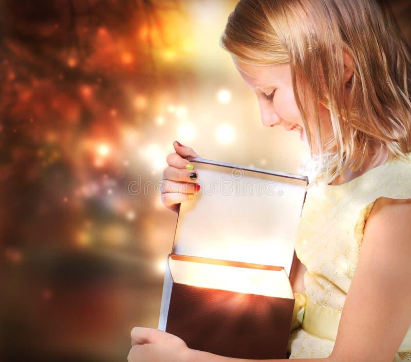 Glückliches Mädchen, das ein Geschenk öffnet stockfotos