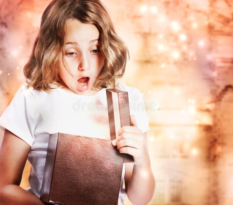 Glückliches Mädchen, das ein Geschenk öffnet stockfotografie