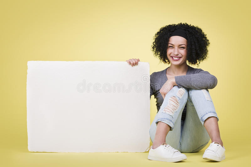 Glückliches Mädchen, das ein Zeichenbrett des leeren Papiers lächelt und hält lizenzfreies stockbild