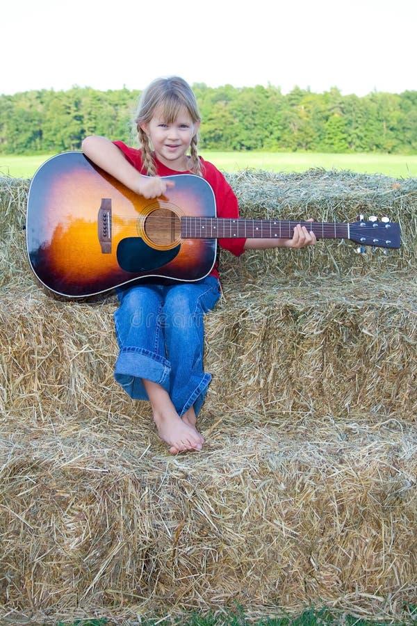 Glückliches Mädchen, das eine Gitarre klimpert. stockbild