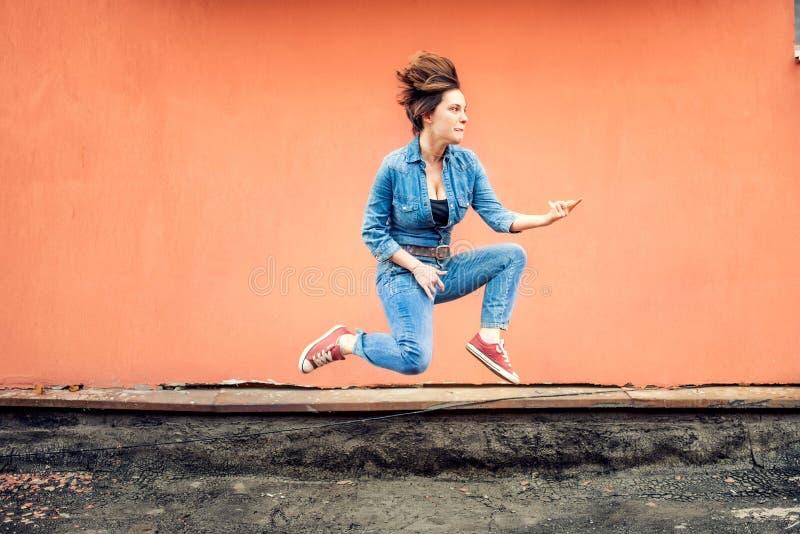 Glückliches Mädchen, das an einem heißen Sommertag springt und singt Modernes Konzept des stilvollen Mädchens herum springend und stockfotografie