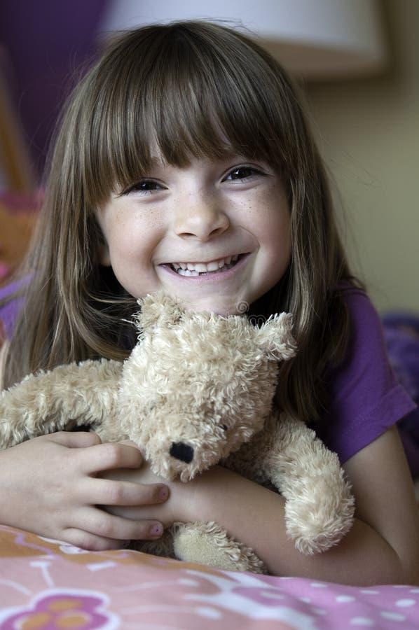 Glückliches Mädchen, das einen Teddybären anhält stockbilder