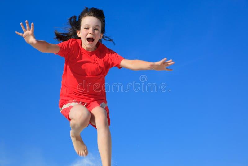 Glückliches Mädchen, das in einer Luft springt stockfotos
