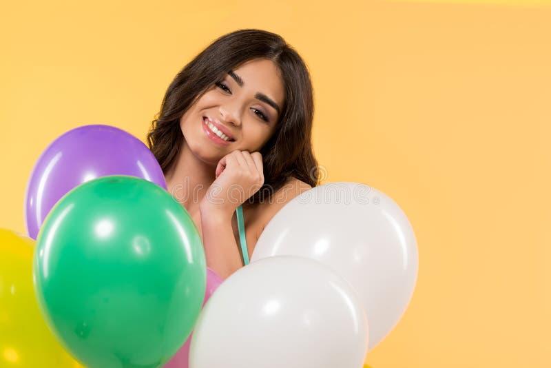 glückliches Mädchen, das im Bikini mit bunten Ballonen aufwirft lizenzfreie stockfotos
