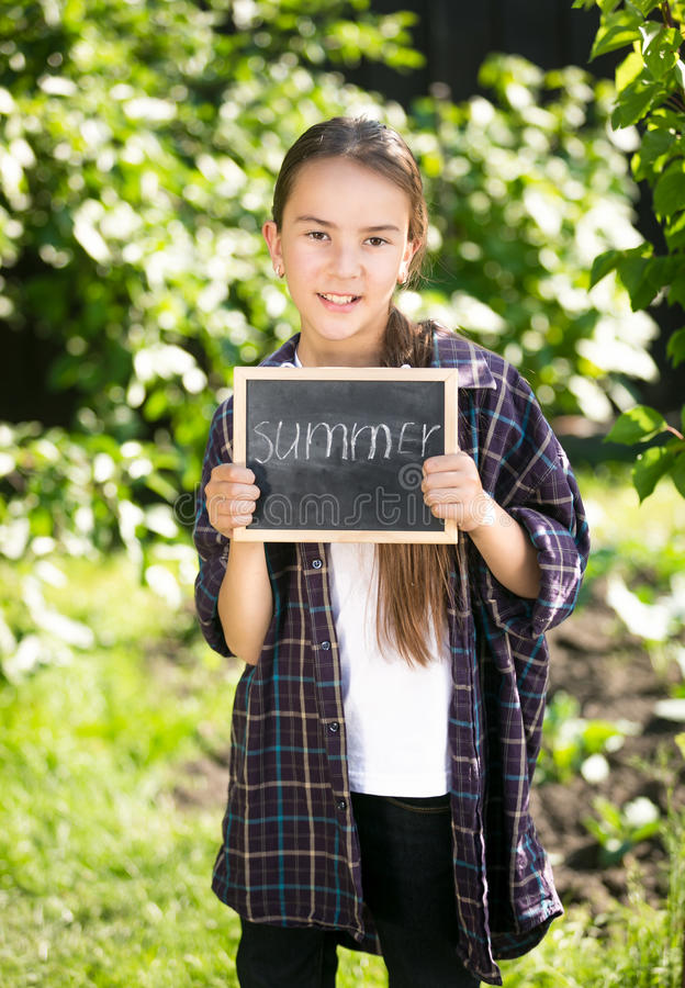 Glückliches Mädchen, das im Garten mit Tafel mit Wort aufwirft stockfoto