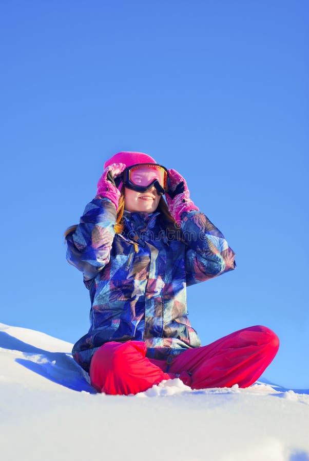 Glückliches Mädchen, das im Schnee sitzt lizenzfreie stockfotos