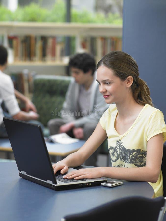 Glückliches Mädchen, das Laptop in der Bibliothek verwendet stockfotos