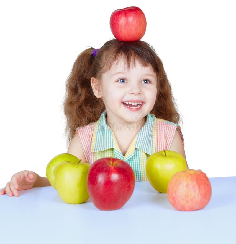 Glückliches Mädchen, das mit den Äpfeln sitzen am Tisch spielt stockbilder