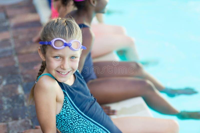 Glückliches Mädchen, das mit Freunden am Poolside sitzt lizenzfreie stockbilder