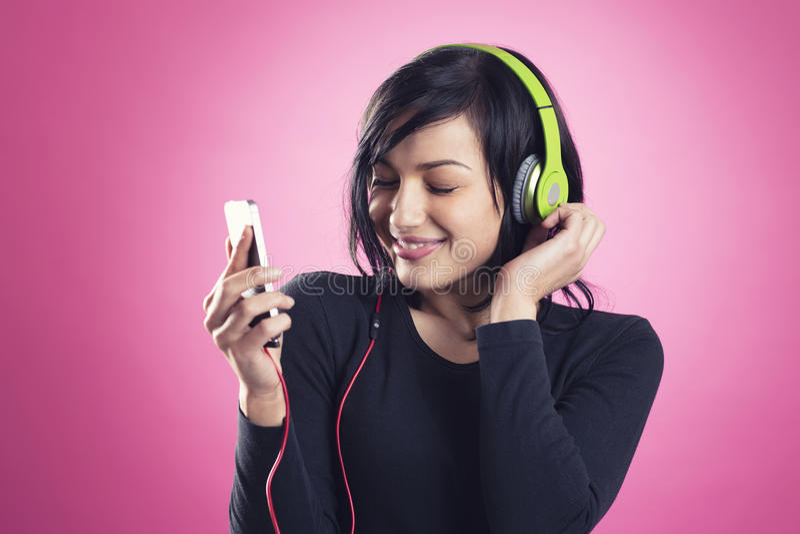 Glückliches Mädchen, das Musik mit Kopfhörern hört stockfoto