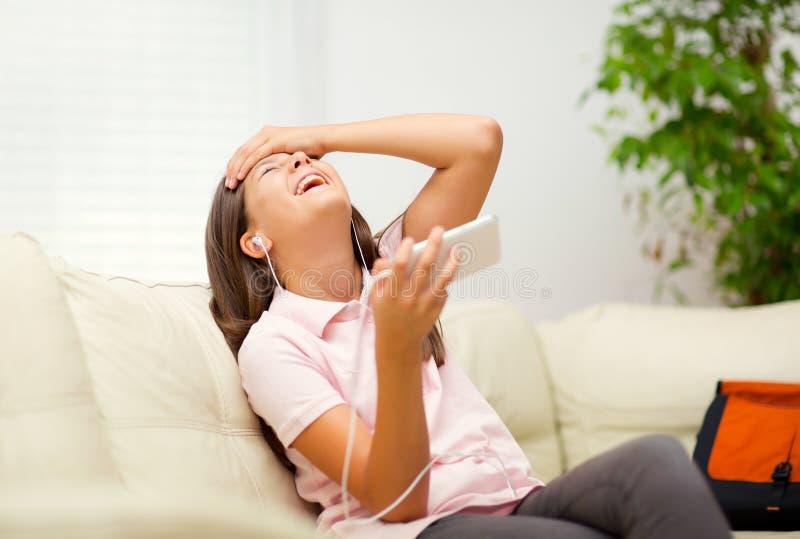 Glückliches Mädchen, das Musik vom Handy hört lizenzfreies stockbild