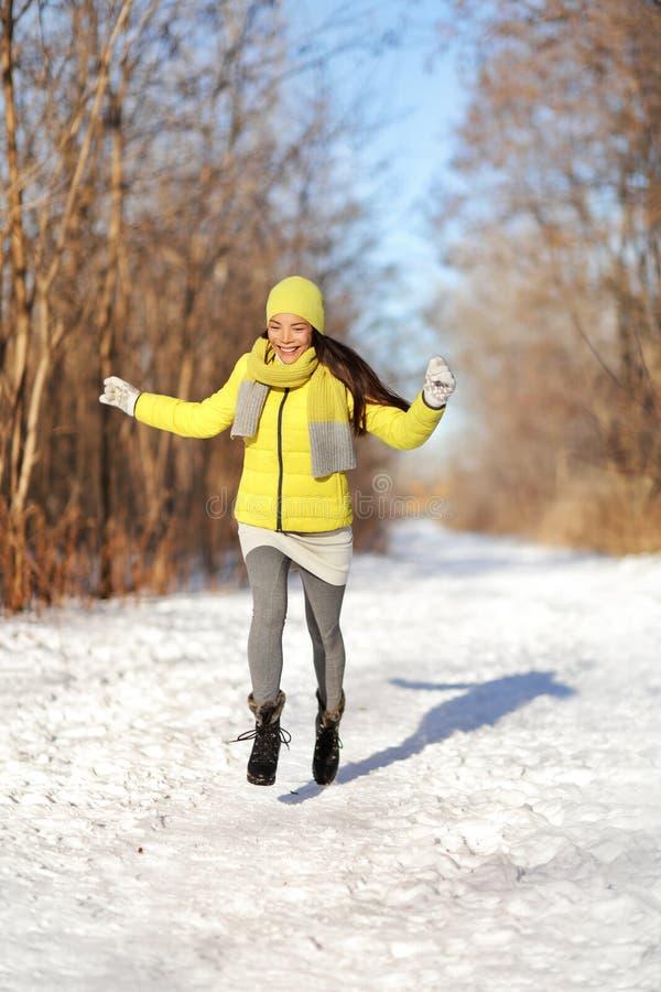 Glückliches Mädchen, das in Schneewinterlandschaft läuft stockfotografie