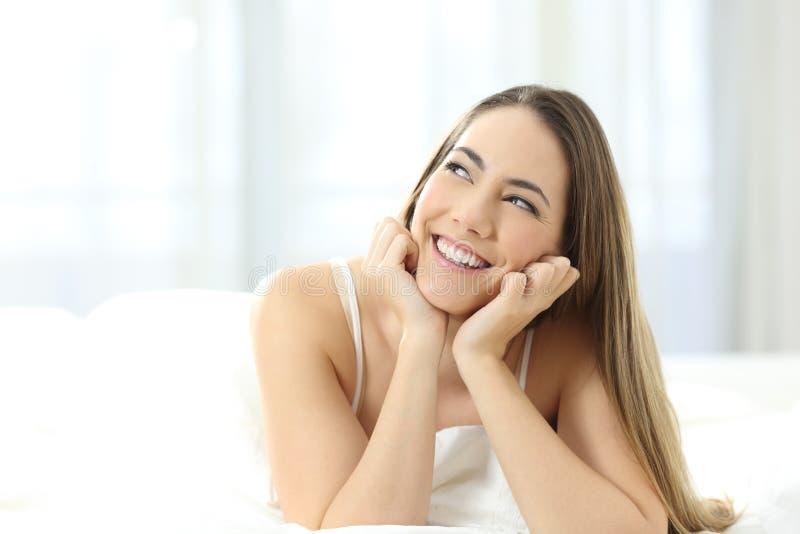 Glückliches Mädchen, das Seite auf einem Bett betrachtend träumt lizenzfreie stockfotos