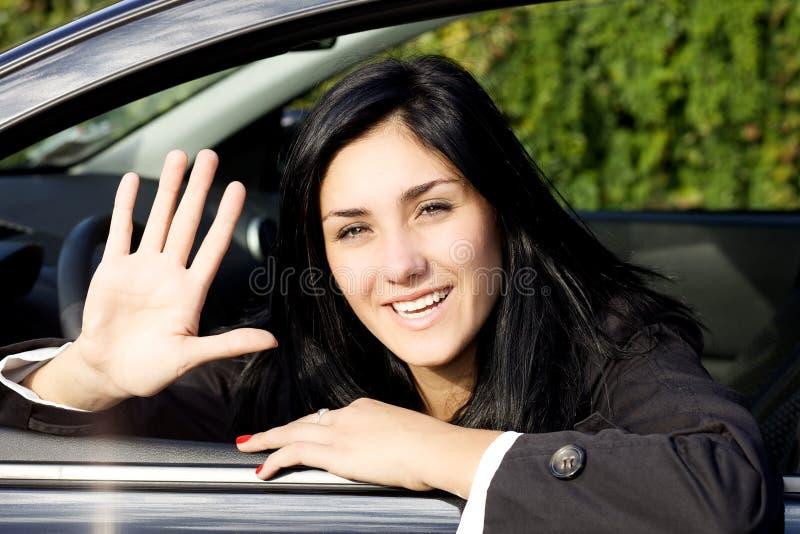 Glückliches Mädchen, das vom Auto schaut Kamera Guten Tag sagt lizenzfreies stockfoto