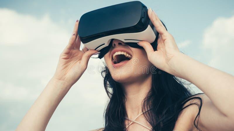 Glückliches Mädchen, das VR-Kopfhörer verwendet Die Zukunft Frau mit Gläsern virtueller Realität Digital-Zukunft und -innovation  lizenzfreie stockbilder