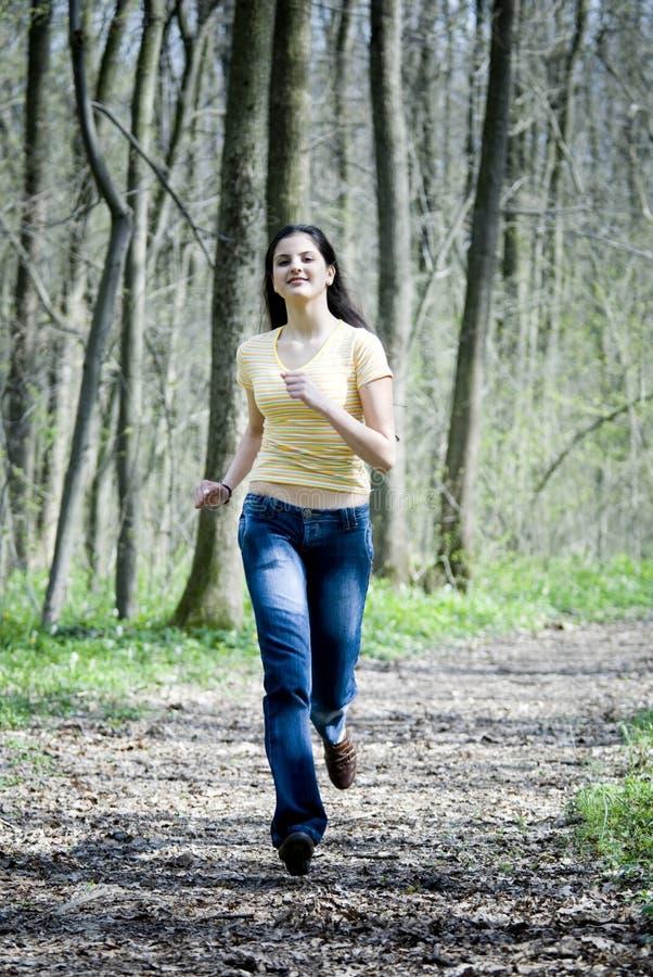 Glückliches Mädchen, das in Wald läuft stockfotos