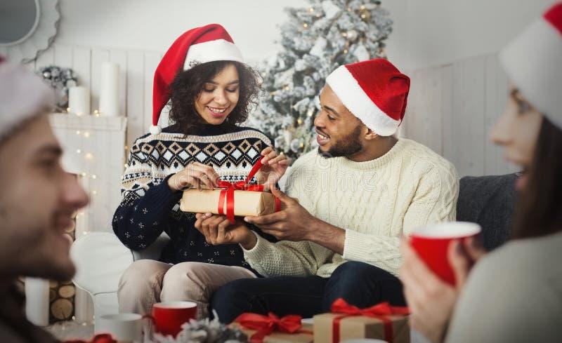 Glückliches Mädchen, das Weihnachtsgeschenk von ihrem Freund auspackt stockbild