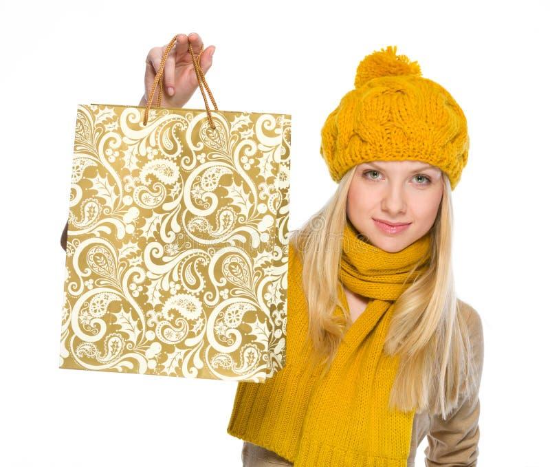 Glückliches Mädchen in der Herbstkleidung, die Einkaufstasche zeigt stockfoto