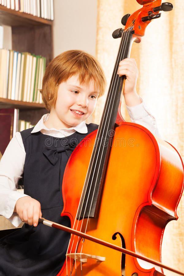 Glückliches Mädchen in der Schuluniform, die auf dem Cello spielt stockfotografie