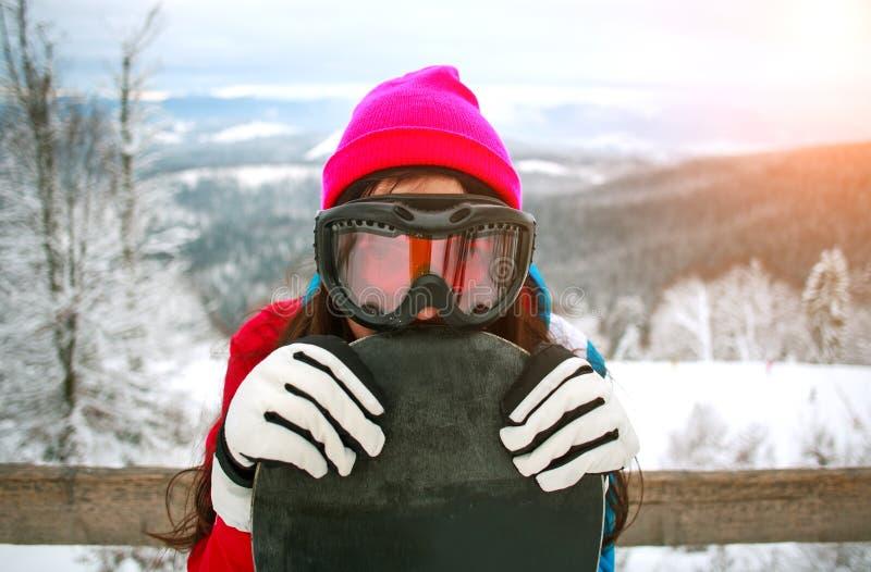 Glückliches Mädchen des Porträts mit Snowboard auf schneebedeckten Berg lizenzfreie stockfotos