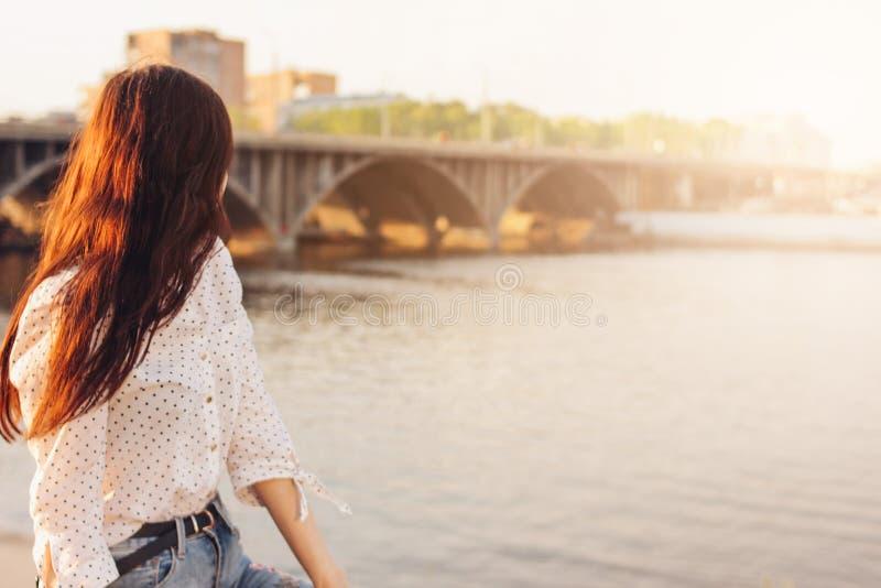 Glückliches Mädchen des positiven schönen langen Haares im weißen Hemd auf Stadtfluss-Brückenhintergrund, Sommerreise-Ferienzeit lizenzfreies stockfoto